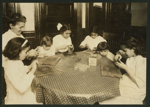 [Woman and children around a table making chains for handbags] Location: [New York, New York (State)]