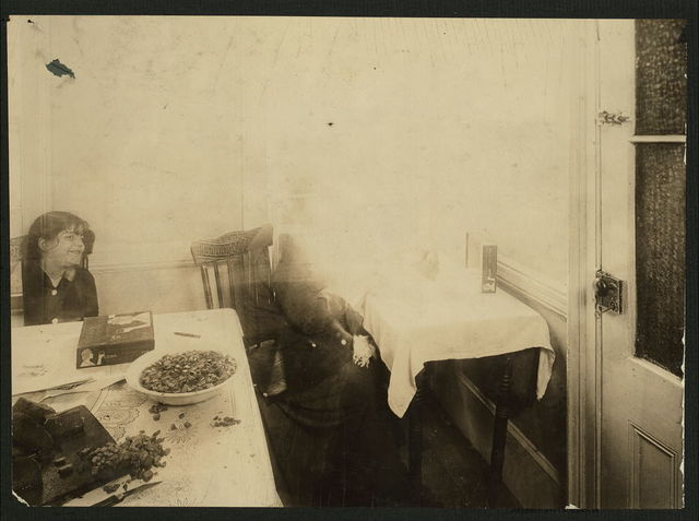 Woman making Turkish Trophy cigarette cases in the kitchen of her East Side Tenement home. Food Scattered about on the table. The door on right is the toilet. (For complete details see Miss E. Watson's report.)  Location: New York, New York (State)