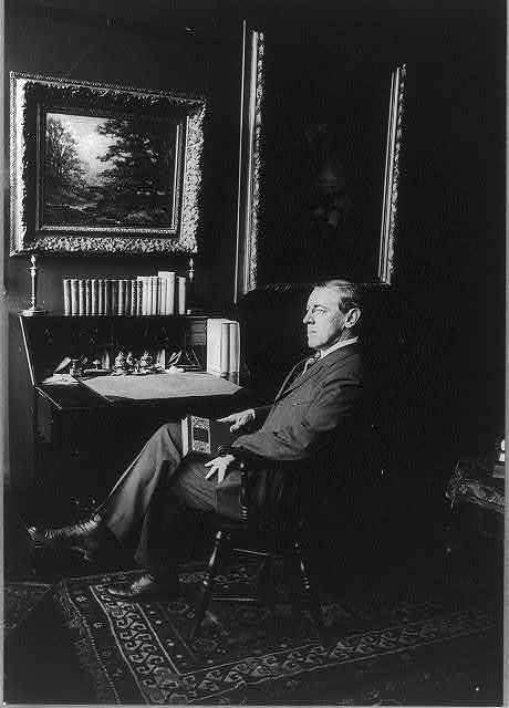 [Woodrow Wilson, full length, seated by desk with book in hand, facing left]