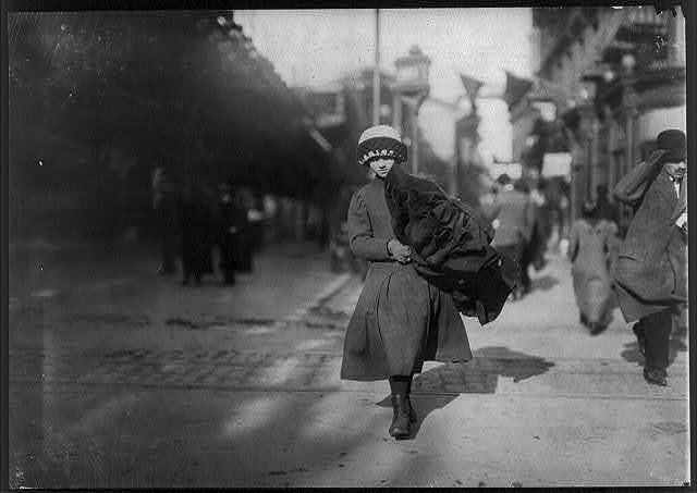 Young girl carrying bundle of coats home to be finished. Near Astor Place, N.Y.  Location: New York, New York (State)
