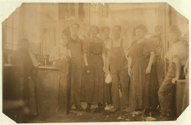 """Young girls working in Seaconnet Mill. The boys and men had just been hauling the girls around and pawing them over in """"rough house"""" as these noon hours sometimes are. Some of the girls make advances to strangers. A very young girl (surely under 14) was helping her mother but refused to pose. Seaconnet Mill.  Location: Fall River, Massachusetts."""