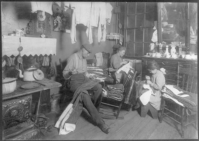 "11:30 A.M. Jennie Rizzandi, 9 year old girl, helping mother and father finish garments in a dilapidated tenement, 5 Extra Pl., N.Y.C. They all work until 9 P.M. when busy, and make about $2 to $2.50 a week. Father works on street, when he has work. Jennie was a truant, ""I staid home 'cause a lady was comin'.-"".  Location: [New York, New York (State)]."