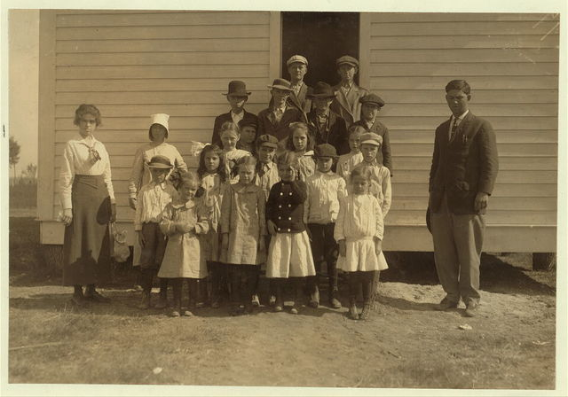 "A group of children at a District School in cotton picking season. Petty's Chapel District School #20, near Corsicana. Only 40 per cent of the children who attend are here because the cotton is still being picked, in most districts the school term is being shortened to accommodate the picking. The children are above the average of country school children and this is an exceptional school, only two of the ten families represented here being ""Renters"" (see Hine Report on Texas). These children are getting 8 months school. Most of the rural schools in Texas give them 6 months or less. All these children, from the 5 year old up pick cotton.  Location: Corsicana [vicinity], Texas."