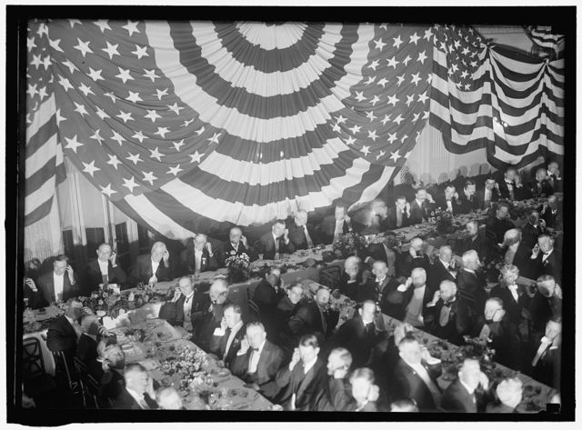 [Banquet scene with flag draping and men seated holding up listening device to one ear]