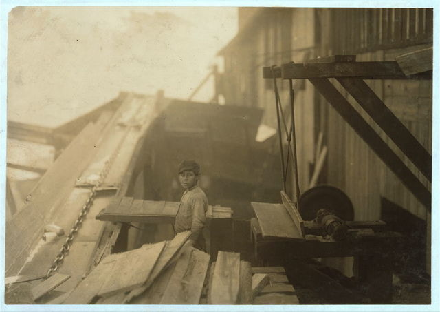 """Dangerous work. Charlie McBride. Said twelve years old. This twelve year old boy has a steady job with the Miller & Vidor Lumber Company. He takes slabs out of a chute which has a moving endless chain to carry the wood up the chute. He passes the slabs onto the other boy who saws them on an unguarded circular saw. Charlie runs the saw himself whenever he gets the chance. He is exposed not only to the above danger, but to the weather - no roof even. Has been here for some months. """"Get four bits a day."""" Fifty cents. Works ten hours. This was the only mill that I found around Beaumont that employed boys, likely because they are located some distance out of town.  Location: Beaumont, Texas."""