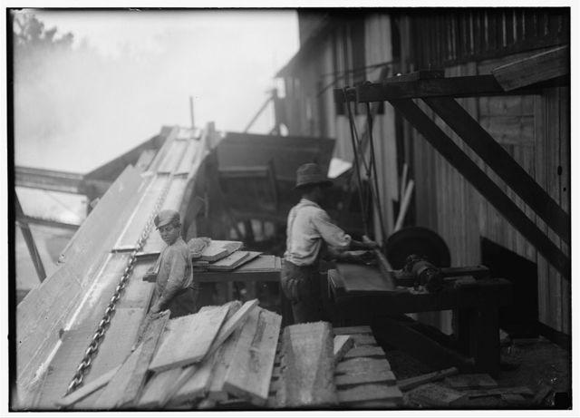 """Dangerous work. Charlie McBride. Said twelve years old. This twelve year old boy has a steady job with the Miller and Vidor Lumber Company. He takes slabs out of the chute which has a moving endless chain to carry the wood up the chute. He passes the slabs on to the other boy who saws them on an unguarded circular saw. Charlie runs the saw himself whenever he gets a chance. He is exposed, not only to the above dangers, but to the weather, no roof even. Has been here for some months. """"Get four bits a day."""" (Fifty cents.) Works ten hours. This was the only mill that I found around Beaumont that employed boys - likely because they are located some distance out of town.  Location: Beaumont, Texas."""