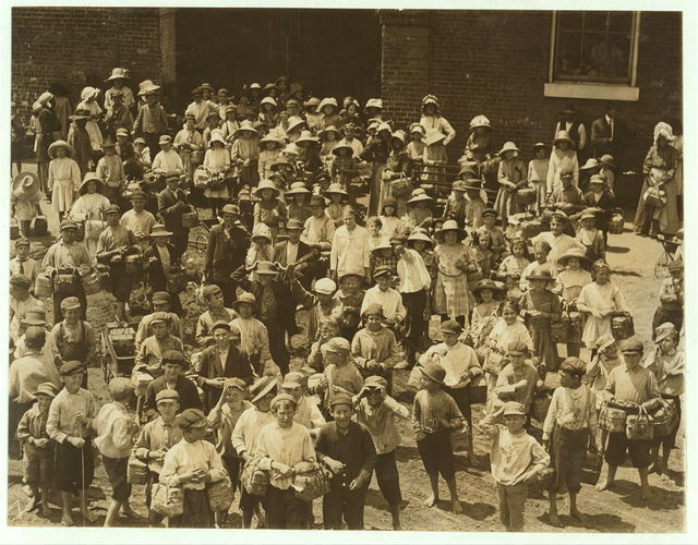 """Dinner-Toters"" waiting for the gate to open. This is carried on more in Columbus than in any other city I know, and by smaller children. (See photos.) Many of them are paid by the week for doing it, and carry, sometimes, ten or more a day. They go around in the mill, often help tend to machines, which often run at noon, and so learn the work. A teacher told me the mothers expect the children to learn this way, long before they are of proper age. (See also Vaughn's Georgia Report, April, 1913.) Eagle and Pho[e]nix Mill.  Location: Columbus, Georgia."