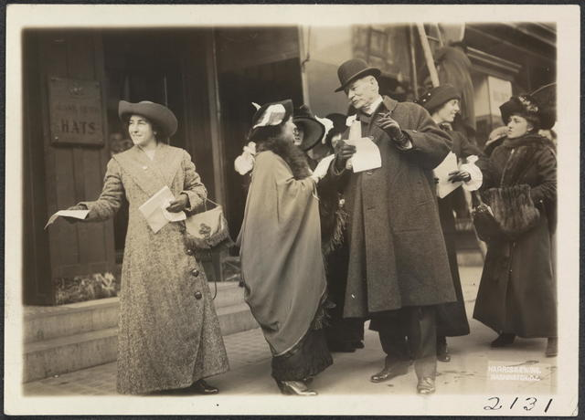 Distributing hand bills advertising Inaugural Suffrage Parade and inviting everyone to participate Jan. [19]13.  Mrs. Wm Kent talking to ? [man not identified]