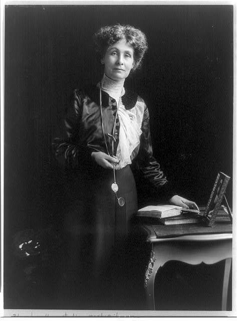 [Emmeline (Goulden) Pankhurst, three-quarter length portrait, standing by small table, facing right, with left hand on book]