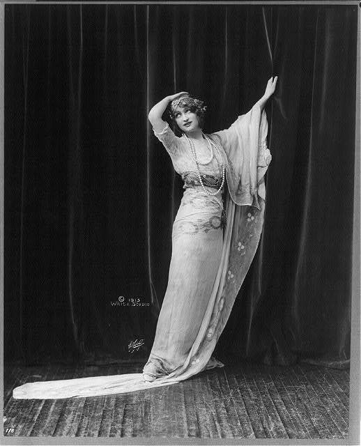 [Gaby Deslys, 1884-1920, full length portrait, standing, facing left, rt. hand on top of head, lt. hand grasping curtain]