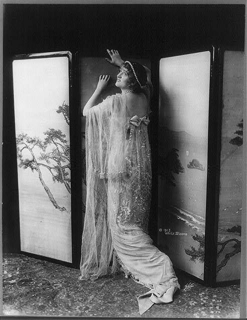 [Gaby Deslys, 1884-1920, full length, standing, facing left, arms against folding partition]