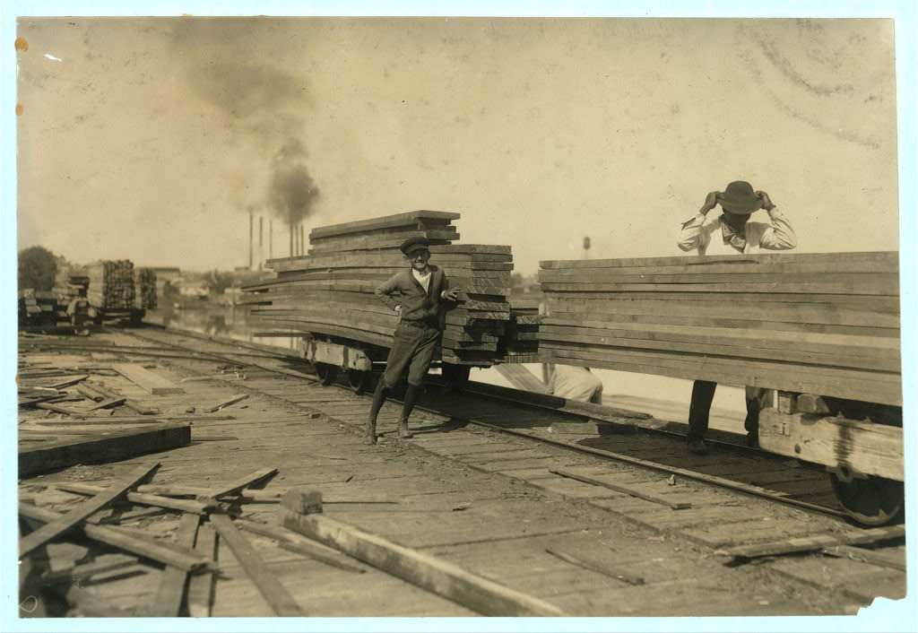 """General Utility Boy at Lutcher & Moore Lumber Co. """"I'm fourteen years old; been here one year. Get $1.00 a day."""" He runs errands and helps around. I saw him pushing some of these empty cars. Exposed to the weather and some danger. In the saw mill and planing mill of this company I saw several boys who might be under fifteen.  Location: Orange, Texas."""