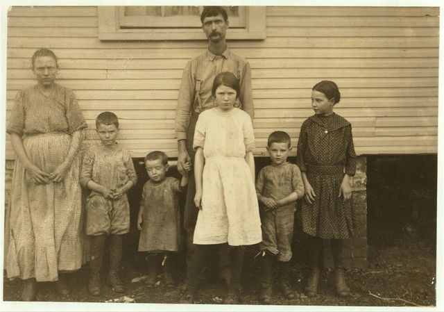 Gracie Clark, 268 A Street (with a white dress) has been a spinner in the filling room of Merrimack Mill for three years. Her Life Insurance Policy gives her age thirteen years now, so she began working at ten years. See Hine report.  Location: Huntsville, Alabama.