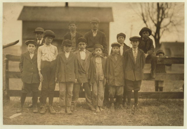 Group of some of the youngest workers in the Merrimack Mills. Everyone (except the boy behind the fence) has a steady job in the Merrimack Mills. See Hine report.  Location: Huntsville, Alabama.