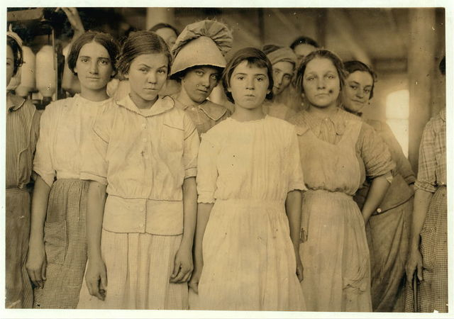 Group of workers in cotton mill at West. Two of them are under legal age. One is twelve and one is fourteen according to their Family Record. Much illiteracy here.  Location: West, Texas.