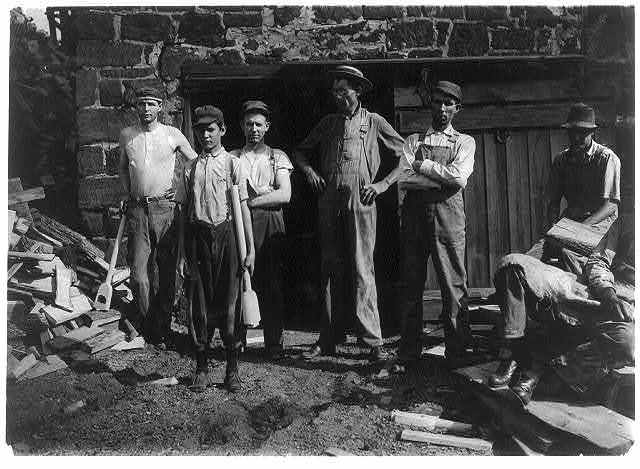 Group outside Pittman Handle Factory. A fifteen year old boy operating a dangerous boring machine at which he said a boy recently bored half his hand off. To operate this machine (which bores a large hole in the spade handle) the boy has to throw his whole weight onto the lever which pushes the handle (and himself) up against the unprotected borer. A slip might easily result fatally. Boy earns $1.65 a day. This factory has a number of unprotected belts and dangerous machines. One other boy, about the age of this one, was doing all kind[s] of work, taking away the handles from a huge rip saw, etc., and constantly exposed to danger. Pittman Handle Factory, Denison, Tex.  Location: Denison, Texas.