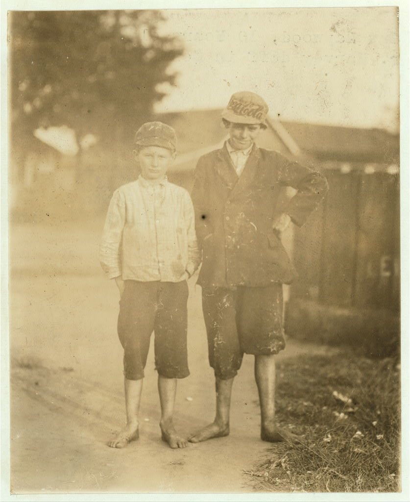 Guy Haywood, 10 years old, helps his brother. Harvey doff[s] in Columbus (Ga.) Mill.  Location: Columbus, Georgia.