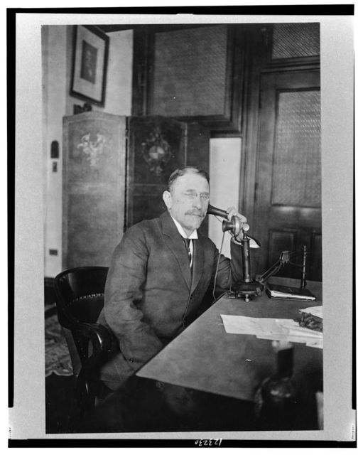 [Henry Morgenthau, half-length portrait, seated at desk, facing right, holding telephone receiver]