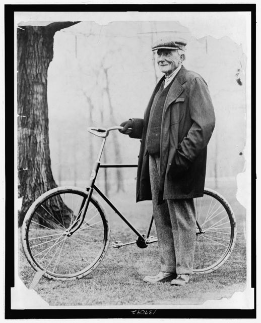 [John D. Rockefeller, full-length portrait, standing with a bicycle]