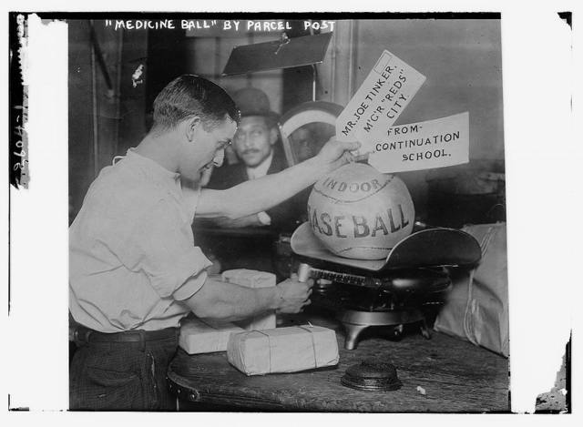 Medicine ball being weighed by Post Office employee; shipping tags read:  Mr. Joe Tinker, Mgr Reds (Cincinnati) From Continuation School.  [1913]