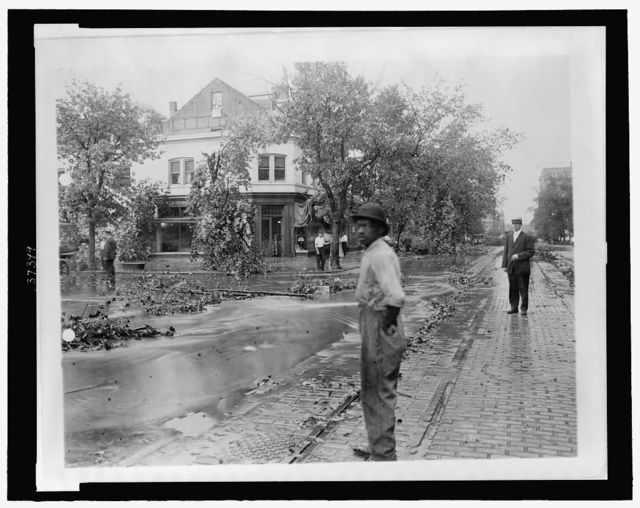 [Men standing looking at tree limbs and other debris and high water in the street after a storm]