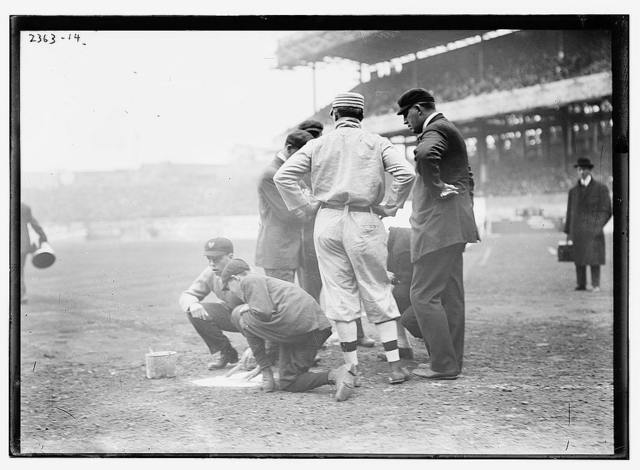 Pre-game activities at home plate involving managers, umpires, and grounds crew