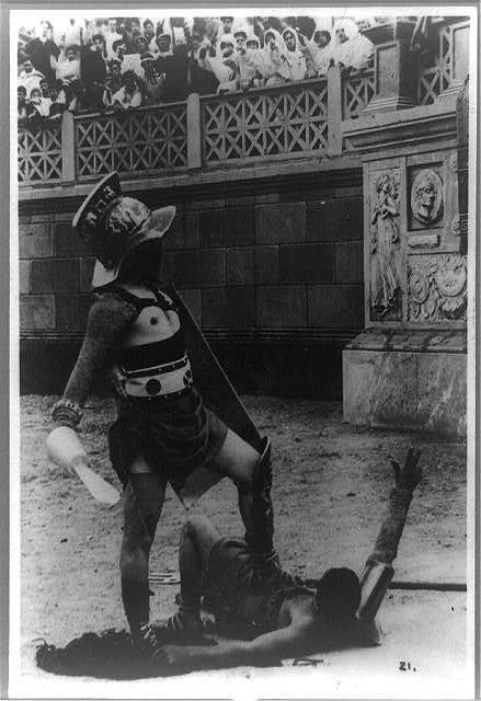"[Scene from film ""Quo Vadis"", showing a gladiator standing over a fallen Christian in arena]"
