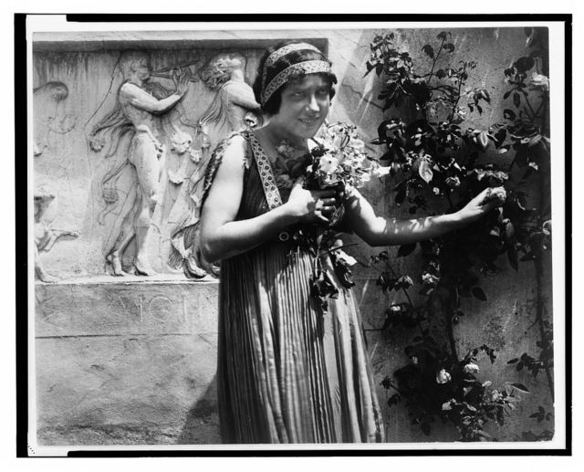 "[Scene from the silent film ""The last days of Pompeii"" showing a young woman clutching flowers to her chest as she picks a rose, bas-reliefs in the background]"