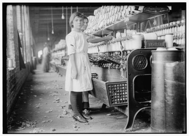 """Twelve year old Selina Wall working at spooling in the Brazos [?] Valley Cotton Mill, West Texas. Their family Record says she was born, March 23, 1901. Her mother said: """"She's just taking the place of her sister fifteen years old. Selina could earn a dollar a day. She was raised up in a cotton mill over in Belton, but she has to stay home and do the cookin."""" The mother and the fifteen year old girl work regularly in the mill. Several older boys work. Selina keeps house. Nine in the family.  Location: West, Texas."""