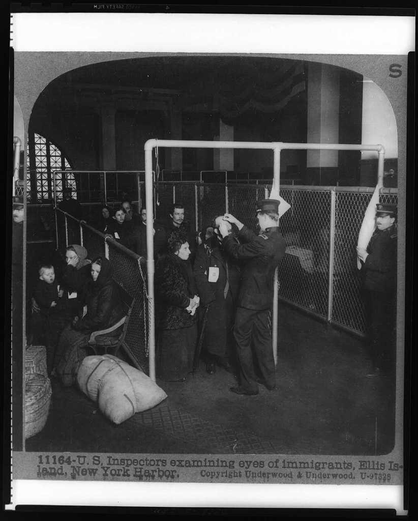 U.S. inspectors examining eyes of immigrants, Ellis Island, New York Harbor