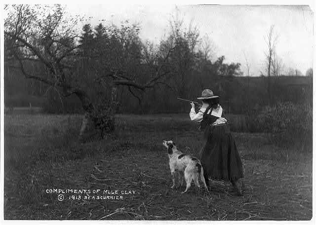 [Woman in cowgirl outfit aiming small rifle; English Setter standing beside her]