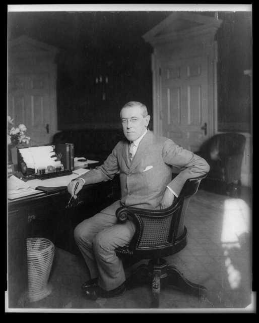 [Woodrow Wilson, full-length portrait, seated at desk, facing slightly left]