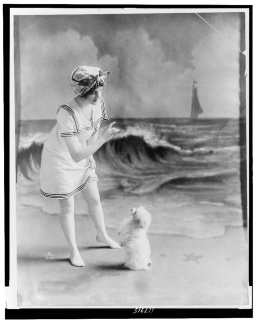 [Young woman in bathing suit with small dog in front of studio backdrop of beach]