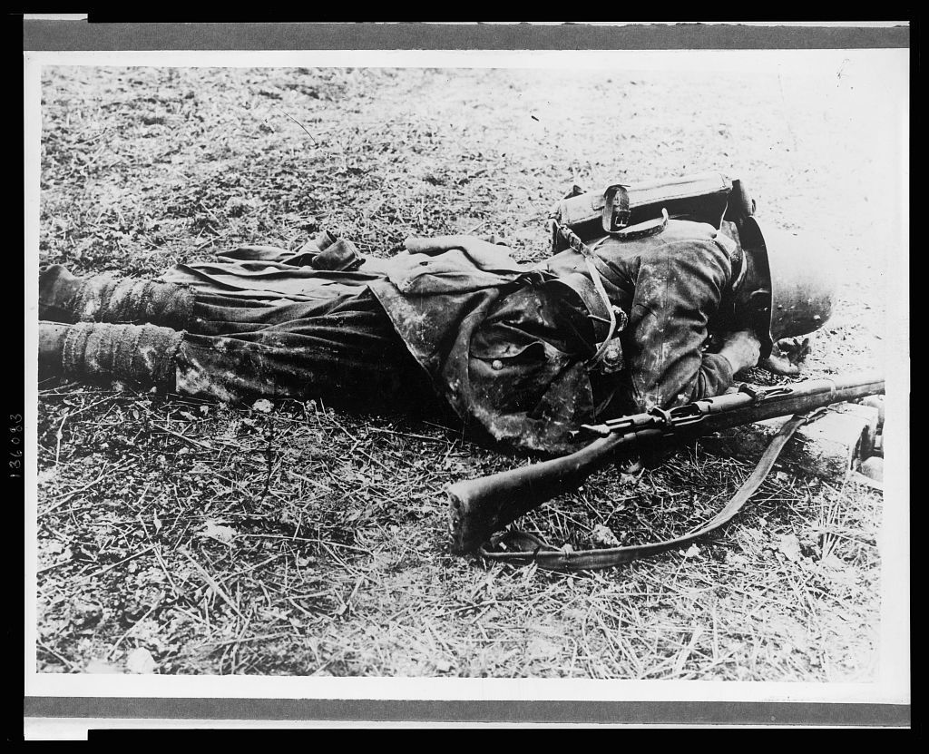 [A German soldier, probably a sniper, laying on the ground ]