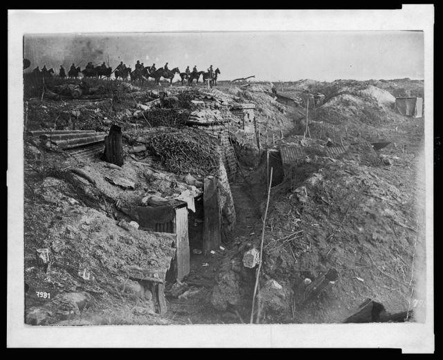 [Abandoned British trench which was captured by the Germans; in background, German soldiers on horseback view the scene]