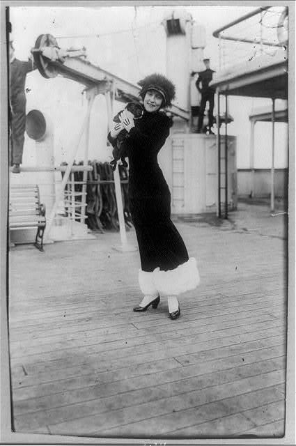 [Annette Kellerman, full-length portrait, standing on deck of ship, facing front, holding a black pug (dog)]