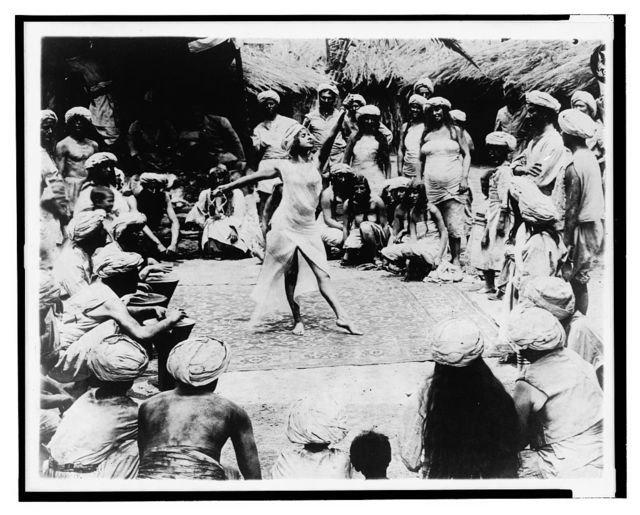 Between savage and tiger. Nautch girl dancing on rug with Hindoo men and women watching