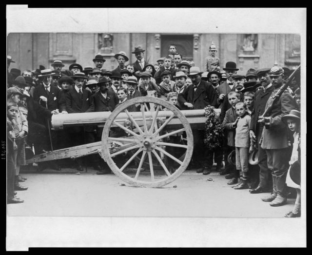 [Crowd of German civilians, including children, surrounding a cannon which has a garland hanging from the muzzle]