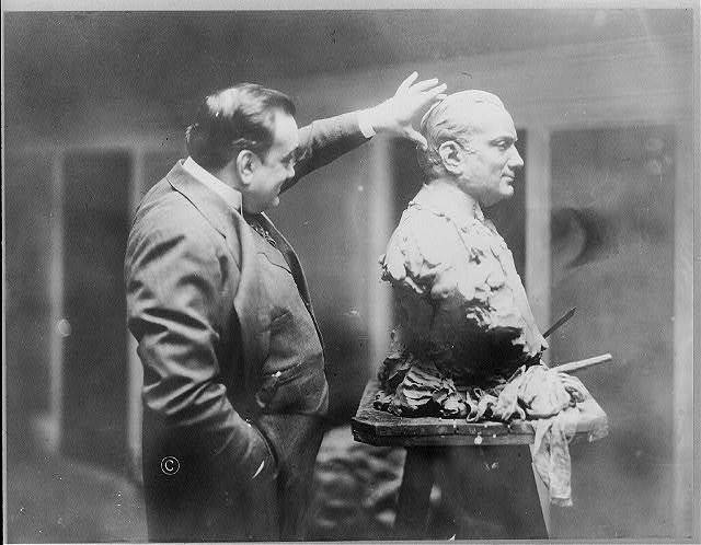 [Enrico Caruso, 1873-1921, three-quarter length portrait, standing, right profile, examining a bust sculpture of himself]