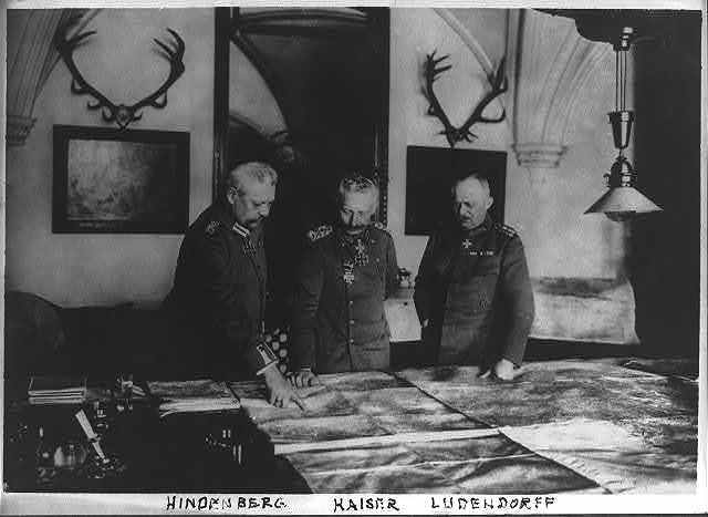 [General Paul von Hindenburg, Kaiser Wilhelm II, and General Erich Ludendorff standing at a table, examining large maps]