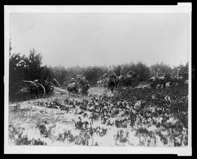 [German soldiers firing artillery gun while other soldiers on horseback move a wagon]