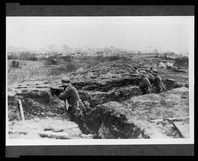 [German soldiers in a trench; in background, a town]