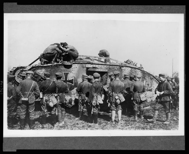 [German soldiers standing around a German tank as other soldiers work on the tank]