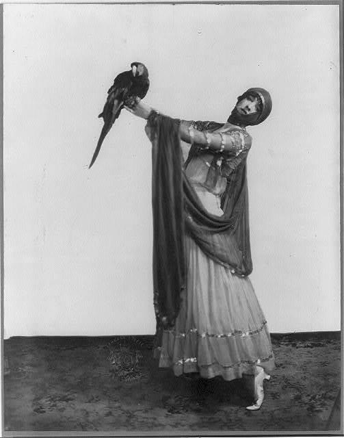 [Gertrude (Vanderbilt) Whitney, 1877-1942, full length, standing, facing slightly left; holding parrot]