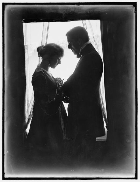 [John Murray Anderson, the theatrical producer, and his wife posed at a window]