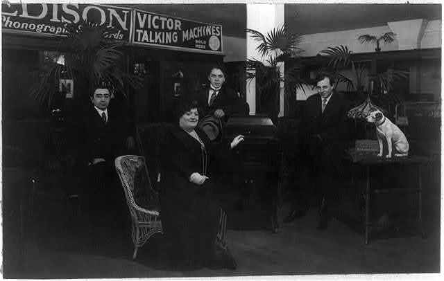 [Luisa Tetrazzini, full-length portrait, seated facing right; with victrola and three men in phonograph store]