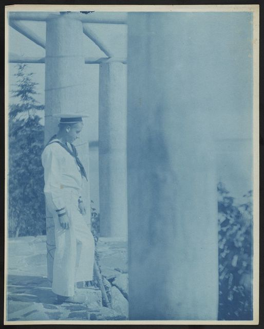 [Maynard White in sailor suit standing beside a column on pergola]
