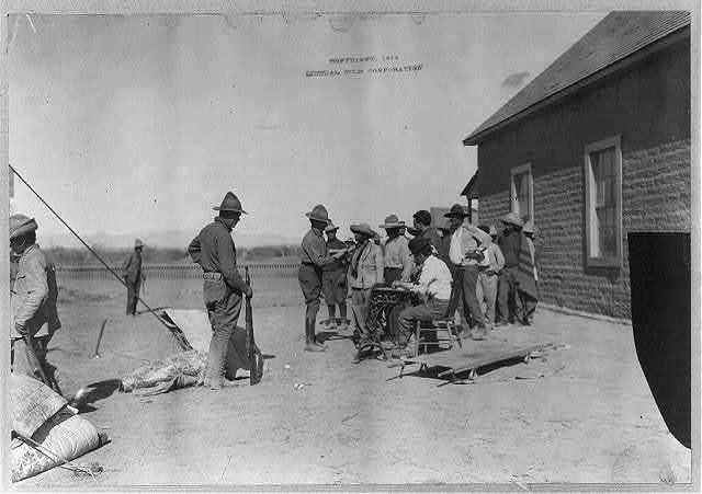 [Mexican War, 1914: U.S. soldiers interviewing Mexican refugees; man wearing bowler hat and Red Cross armband seated in center]