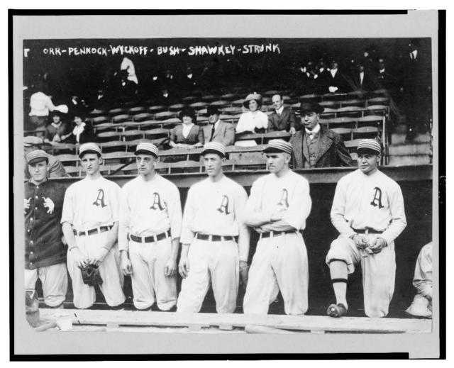 [Players for the Philadelphia Athletics from left to right: Billy Orr, Herb Pennock, Weldon Wyckoff, Joe Bush, Bob Shawkey, Amos Strunk, standing in front of a dugout]