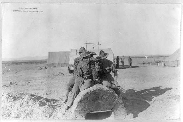 [U.S. Army tent camp in Mexico, 1914: 3 soldiers sitting atop field oven with baby goat]